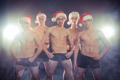 Sexy muscular men in Santa form. Christmas New Year. Sexy muscular men in a Santa shape on a dark smoky background. Christmas New Year Royalty Free Stock Photos