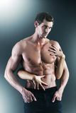 Sexy muscular naked man and female hands. Holding his chest Royalty Free Stock Photography