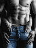 Guy. Muscular naked man and female hands unbuckle his jeans on a dark background