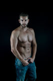 Sexy muscular young man. Young handsome bearded man sexy macho with muscular hands and beard on serious face with naked torso posing in studio on black Stock Photo