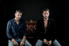 Sexy muscular young men. Two young handsome bearded muscular men sexy macho with beard on serious face in stylish jacket and shirt posing in studio sitting on Stock Images