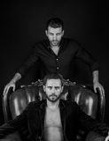 Muscular young men. Two young handsome bearded muscular men macho with beard on serious face in stylish jacket and shirt posing in studio sitting on leather royalty free stock photo