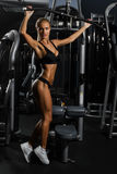 Sexy, muscular young woman in underwear posing against gym, full body figure. Rear view of sexy, muscular young woman in underwear posing against gym, full body Royalty Free Stock Photos