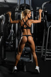 Sexy, muskulöse junge Frau in der Unterwäsche, die gegen Turnhalle, volle Körperzahl aufwirft Lizenzfreie Stockfotos