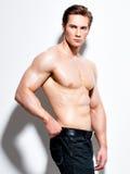 Sexy muskulöser junger Mann, der Kamera betrachtet Stockfotografie