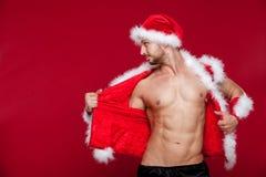 Sexy muskulöser Mann in Sankt-Uniform Weihnachten neu Stockfotos