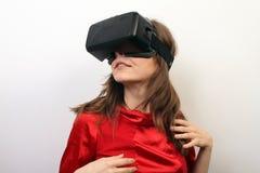 Sexy, mysteriöse Frau in einem roten Kleid, tragender Kopfhörer virtuellen Realität 3D der Oculus-Riss-VR, intrigierte Stockfotos