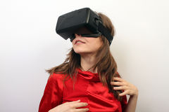Sexy, mysterious woman in a red dress, wearing Oculus Rift VR Virtual reality 3D headset, intrigued Stock Photos