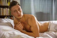 Sexy naakte jonge mens op bed royalty-vrije stock afbeeldingen