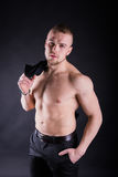 Sexy nackter Torso des jungen Mannes mit Hemd in seinen Händen auf einem dunklen Hintergrund Stockfoto