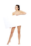 Sexy naked brunette holding empty board Stock Photography