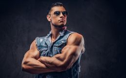 Naked fashionable athletic man in a denim vest and sunglasses poses with crossed arms in a studio. Isolated on dark background Royalty Free Stock Photography