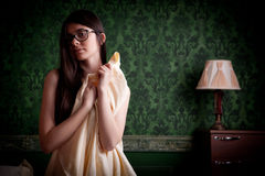 Sexy naked girl with bed sheets in hands on green vintage wall Royalty Free Stock Image
