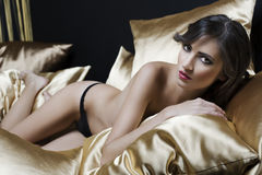 Sexy naked girl between pillow Stock Images