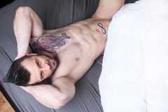 A sexy naked man lay in the bed Stock Image
