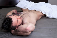 Sexy naked man lay in the bed Royalty Free Stock Photography