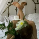 Naked woman relaxing on a bed with a cup of tea on her buttocks.