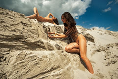 Sexy naked women relax on flowing sand Royalty Free Stock Photos
