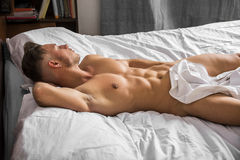Sexy naked young man on bed Royalty Free Stock Photography