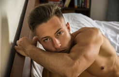 Sexy naked young man on bed. Totally naked sexy young man with muscular body on bed looking away Stock Photography