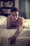 Sexy naked young man on bed. Totally naked sexy young man with muscular body on bed looking at camera Royalty Free Stock Photos