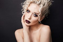 Sexy naked young woman with dark red full lips and with beautiful blue eyes, with blond curly hair and professional. Bright makeup, isolate at black background stock photos