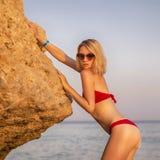 Sexy nehmen Sie geeignete blonde kaukasische junge Frau im roten herrlichen Schwimmen ab Stockfoto