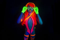 Sexy neon uv glow dancer. Sexy female disco dancer poses in UV costume Royalty Free Stock Images