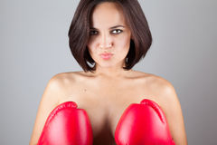 Sexy nude girl  covering her breast with boxing gloves. Beautiful young kissing nude sexy girl woman athlet, covering her breast with boxing gloves,  studio Royalty Free Stock Image