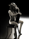 Sexy nude woman sitting on a chair wearing a cowboy hat Stock Photo