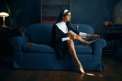 Sexy nun paints her toenails with nail polish