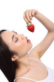 oriental girl eating red strawberry fruit Royalty Free Stock Photos