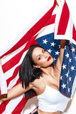 Patriot brunette woman holding USA flag. At white wall, patriotism royalty free stock image