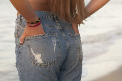Sexy perfect woman in jeans against the sea. back view. Middle body parts. Fashion. Advertising of fashionable jeans. Stock Images