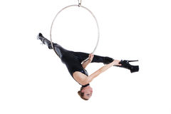 Sexy performer in latex outfit hanging on aerial hoop Stock Photo