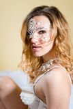 Sexy pertty girl in white mask over cream Royalty Free Stock Images