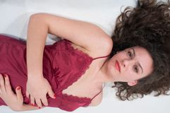 young woman with curly hair, half-length lying, detail of wavy and curly hair and petticoat Fashion Woman Underdress Female L royalty free stock images