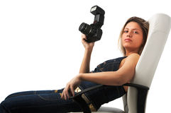 Sexy photographer. Sexy girl with camera is sitting in white leather office chair Stock Image