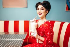 Sexy pin up girl drinks milkshake through a straw. Sexy pin up girl with make-up drinks milkshake through a straw in retro cafe, popular american fashion 50s and Royalty Free Stock Image
