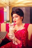 Sexy pin up girl drinks milkshake through a straw. Sexy pin up girl with make-up drinks milkshake through a straw in retro cafe, popular american fashion 50s and Royalty Free Stock Photo