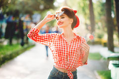 Sexy pin up girl with lollipop walks in a park Stock Photography