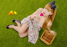 Sexy pin up girl lying in grass with a lollipop Stock Photo