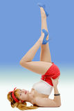 Sexy pin-up girl in shorts and high heels lying on a floor Royalty Free Stock Images