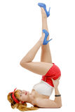 Sexy pin-up girl in shorts and high heels lying on a floor Royalty Free Stock Image