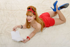 Sexy pin-up girl in shorts and high heels lying on a floor Stock Photography