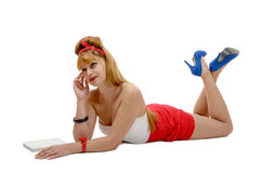 pin-up girl in shorts and high heels lying on a floor Royalty Free Stock Photos