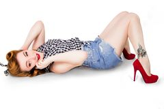 Sexy pin-up girl in shorts and high heels lying on a floor with mobile phone lizenzfreie stockfotos