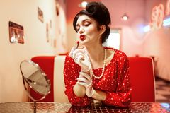 Sexy pin up woman with bright lipstick in hand. Sitting against mirror, dress with polka dots, vintage style. Retro cafe 50 american fashion Stock Photos