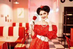 Sexy pin up woman with make-up holds red rose. Dress with polka dots, vintage style. Retro cafe interior with checkerboard  floor Royalty Free Stock Photography