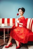 Sexy pin up woman with make-up holds red rose. Dress with polka dots, vintage style. Retro cafe interior with checkerboard floor Stock Image
